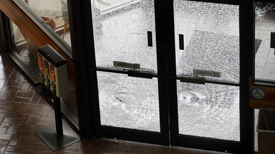 Doors filled with broken glass are photographed after authorities shot and killed a man who they say opened fire on the Mexican Consulate, police headquarters and other downtown buildings early Friday, Nov. 28, 2014, in Austin, Texas. The gunman fired more than 100 rounds at downtown buildings early Friday before he died, Austin authorities said. (AP Photo/Austin American-Statesman, Laura Skelding) AUSTIN CHRONICLE OUT, COMMUNITY IMPACT OUT, INTERNET AND TV MUST CREDIT PHOTOGRAPHER AND STATESMAN.COM, MAGS OUT