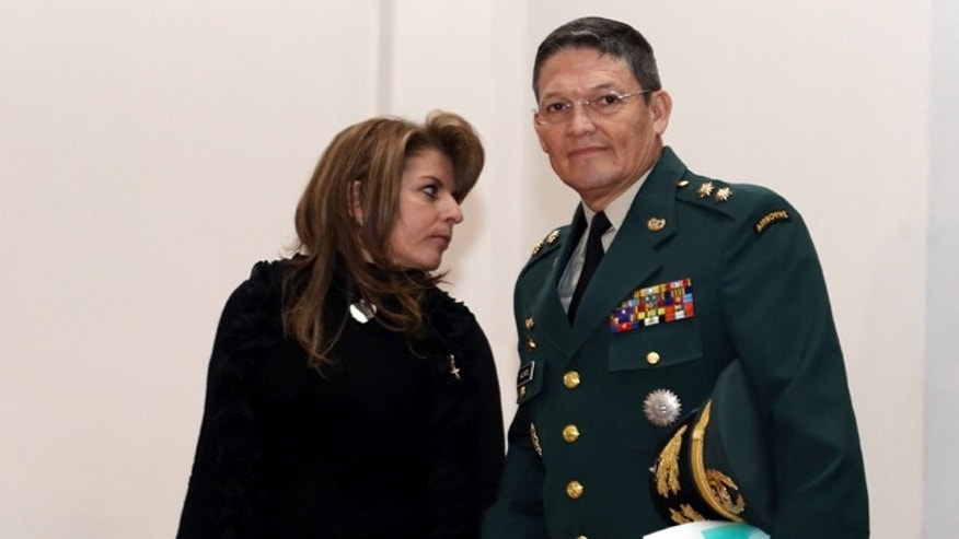 Army Gen. Ruben Alzate arrives with his wife, Claudia Farfan to read a statement for the press at the military hospital in Bogota, Monday, Dec. 1, 2014. Alzate, who was freed by rebels of the Revolutionary Armed Forces of Colombia on Sunday, two weeks after he and two companions were kidnapped by guerrillas, tendered his resignation and said he dishonored the uniform he's worn for 30 years by not following military protocol and venturing up a rebel-dominated river without a bodyguard and dressed as a civilian. (AP Photo/Fernando Vergara)