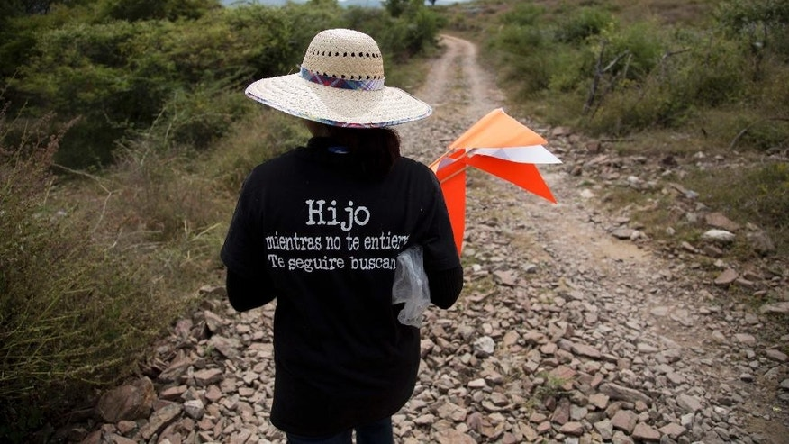 """In this Nov. 29, 2014 photo, a woman with a shirt that reads in Spanish """"Son, if I have not buried you, I will keep looking for you,"""" walks on a hill searching for his family on the outskirts of Iguala, Mexico.  More than 22,300 people have gone missing in Mexico in the past eight years by the government's count, a number that human rights activists believe to be much higher given the expanses of the country controlled by organized crime. Among the disappeared are the 43 students from the Rural Normal School of Ayotzinapa, who were taken by Iguala police Sept. 26 and allegedly turned over to members of the Guerreros Unidos drug gang that rules over much of the state.  (AP Photo/Eduardo Verdugo)"""