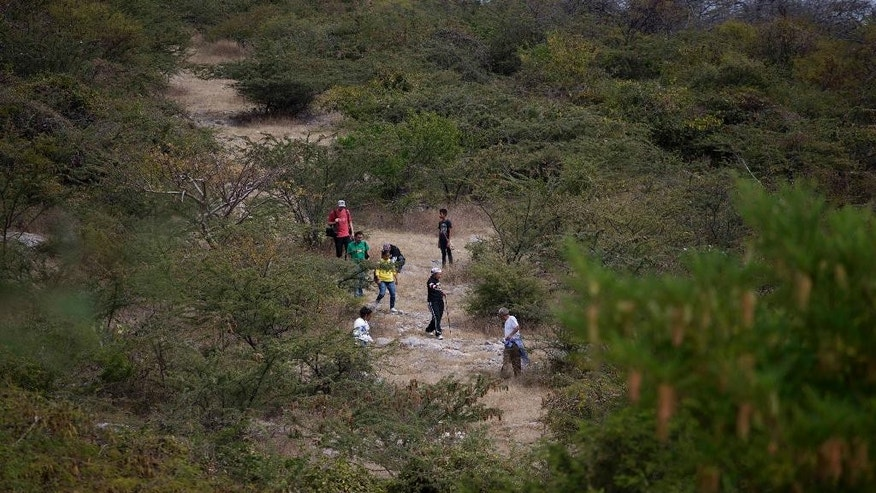 In this Nov. 29, 2014 photo, relatives of missing walk on a hill searching for missing family, on the outskirts of Iguala, Mexico. For many, the digging follows months of combing hospitals, jails and morgues, and sometimes years of false hope. (AP Photo/Eduardo Verdugo)