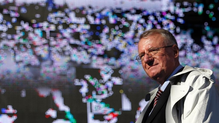 In this photo taken Saturday, Nov. 15, 2014, Serbian ultranationalist leader Vojislav Seselj looks at his supporters during the rally in Belgrade, Serbia. Putin and Russia ties also were strongly featured last week at an ultranationalist rally in Belgrade when 10,000 people cheered Vojislav Seselj, Serbian Prime Minister Aleksandar Vucic's former party boss now on provisional release from the U.N. war crimes tribunal. Evoking hate speech that marked Milosevic's era, Seselj said Serbia should scrap EU integration and turn entirely toward Russia. (AP Photo/Darko Vojinovic)