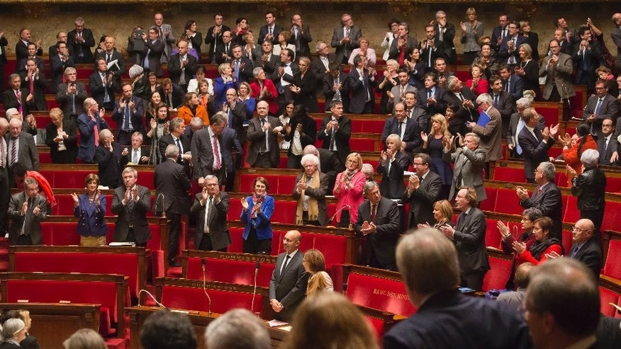 Members of French parliament, applaud after the vote for the recognition of the Palestinian State in Paris, Tuesday, Dec. 2, 2014, as opposition members leave the hall in foreground.