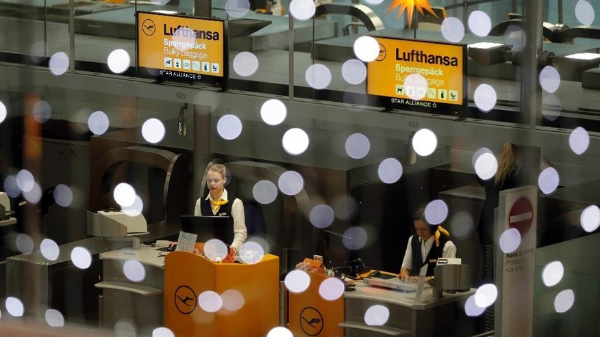 Lufthansa employees wait for customers beside Christmas decoration at the airport in Munich, southern Germany, Tuesday, Dec. 2, 2014. German airline Lufthansa said it has cancelled about half of its flights after pilots went on strike in an ongoing dispute over retirement benefits. (AP Photo/Matthias Schrader)