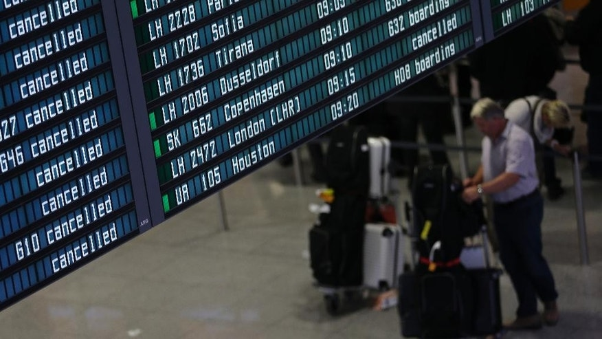 Passengers stand behind a flight board listing canceled flights at the airport in Munich, southern Germany, Tuesday, Dec. 2, 2014. German airline Lufthansa says it has canceled about half of its flights after pilots went on strike in an ongoing dispute over retirement benefits. The airline, Germany's largest, said Monday that 1,350 of its 2,800 flights scheduled through the strike's end Tuesday at midnight have been canceled, affecting 150,000 passengers. The strike was primarily focused on Lufthansa's inner-Europe flights on Monday but was to be extended to long-haul flights Tuesday. (AP Photo/Matthias Schrader)