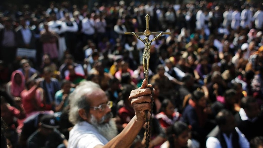 """An elderly Indian Christian holds high a crucifix during a protest after a fire destroyed a church on Monday, outside Delhi police headquarters in New Delhi, India, Tuesday, Dec. 2, 2014. While the cause of the fire is not known, the Delhi Catholic Archdiocese said Tuesday that """"mischief"""" was suspected. Christians account for about 2.5 percent of the country's 1.2 billion people and largely coexist peacefully. However, the issue of conversions by Christian missionaries has sporadically provoked violence by Hindus. (AP Photo/Altaf Qadri)"""