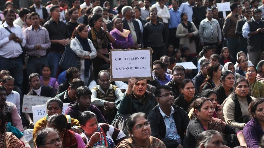 """A protestor holds a placard during a rally organized after a fire destroyed a church on Monday, outside Delhi police headquarters in New Delhi, India, Tuesday, Dec. 2, 2014. While the cause of the fire is not known, the Delhi Catholic Archdiocese said Tuesday that """"mischief"""" was suspected. Christians account for about 2.5 percent of the country's 1.2 billion people and largely coexist peacefully. However, the issue of conversions by Christian missionaries has sporadically provoked violence by Hindus. (AP Photo/Altaf Qadri)"""