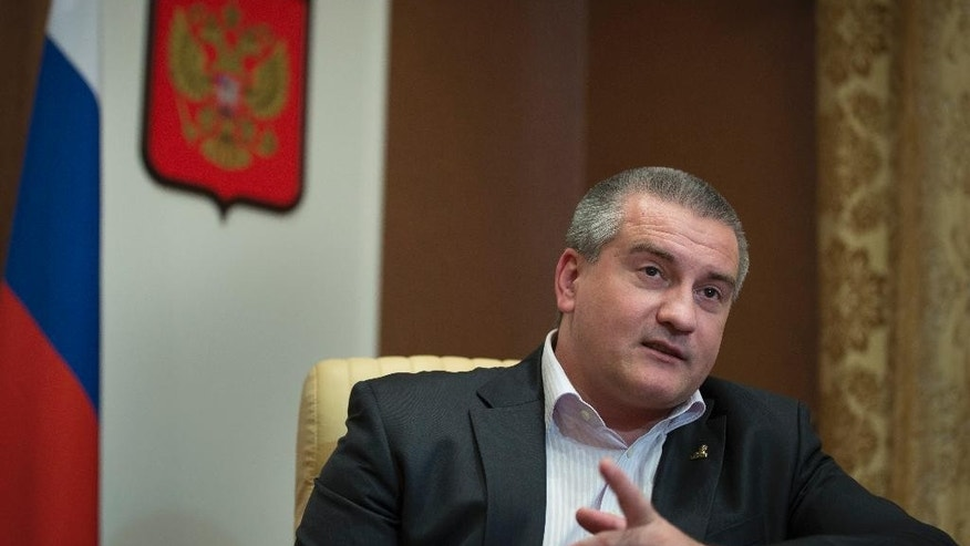 In this photo taken on Thursday, Oct.  30, 2014, Prime Minister of Crimea Sergei Aksyonov speaks during an interview to the Associated Press in Simferopol, Crimea. Aksyonov has defended the decision to forcibly take over dozens of businesses and properties since coming to power in March, saying that the new pro-Moscow government must right wrongs committed by corrupt Ukrainian oligarchs. (AP Photo/Alexander Zemlianichenko)