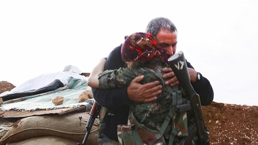 In this image made from a video taken in late November, 2014, Kurdish fighters Pervin Kobani, 19, and her father,  Farouk, embrace in Kobani, Syria. On the front lines of the battle for Kobani, Kurdish female fighters have been playing a major role in helping defend the Syrian town from an onslaught by the Islamic State extremist group. Pervin Kobani is one of them. Three weeks ago, Pervin bumped into her father on a street corner. She was surprised to see him holding a gun. She didn't know that he too had decided to fight. She says he is now her comrade first and foremost _ but hugged him like a father anyway.(AP Photo/Jake Simkin via AP video)