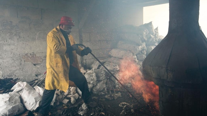 Worker stokes up the fire inside a metal foundry that is destroying weapons sized by Kosovo authorities near the town of Ferizaj on Tuesday, Dec. 2, 2014. Kosovo authorities destroyed over 2,000 small arms and rifles on Tuesday as part of an ongoing effort to increase security in the Balkan country. (AP Photo/Visar Kryeziu)