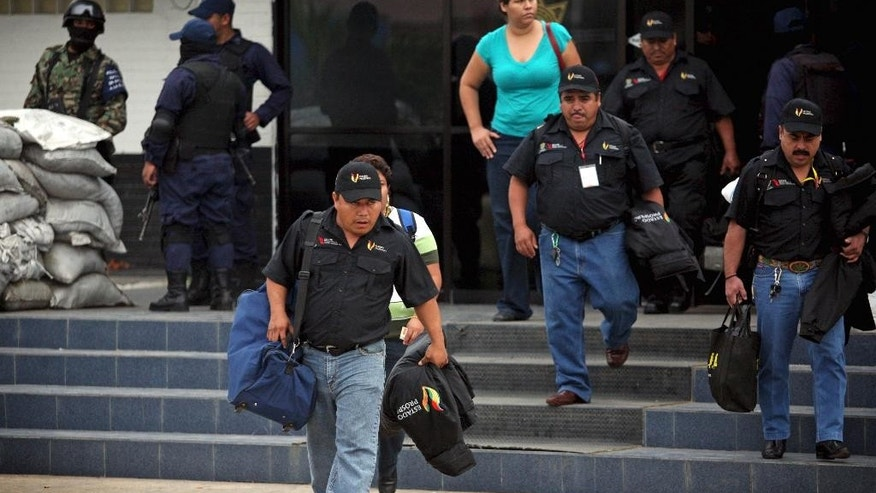 FILE - In this Dec. 21, 2011 file photo, municipal police officers leave a police station after the entire police force was disbanded and temporarily replaced with the Navy, as part of an effort to root out police corruption in Veracruz, Mexico. On Monday, Dec. 1, 2014, Mexico's President Enrique Pena Nieto submitted a bill to Congress that would replace more municipal police, particularly in the states of Guerrero, Tamaulipas, Jalisco and Michoacan, with state police within two years. If passed, the rest of Mexico's 31 states would have presumably more time to implement the police reforms. (AP Photo/Felix Marquez, File)