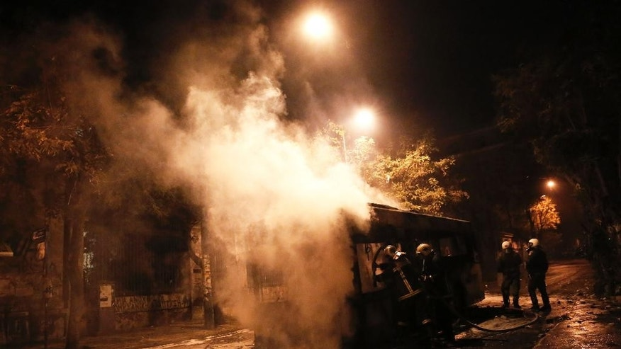 Firemen try to extinguish a bus clashes during between anarchists and police in central Athens, on Tuesday, Dec 2, 2014. The violence followed a large demonstration Tuesday in support of a jailed anarchist Nikos Romanos who is on hunger strike seeking prison leave to attend university. (AP Photo/Petros Giannakouris)