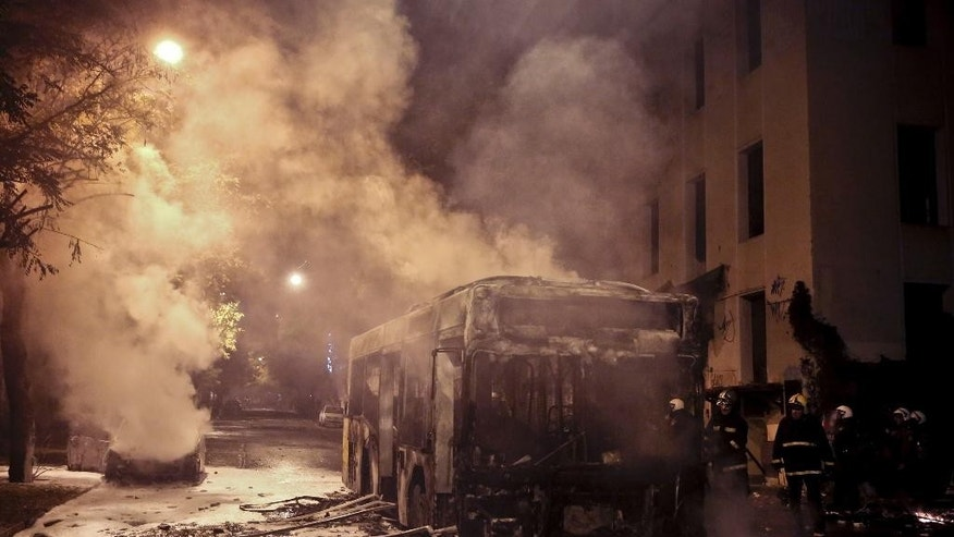 Firemen try to extinguish a bus and a car during clashes between anarchists and police in central Athens, on Tuesday, Dec 2, 2014. The violence followed a large demonstration Tuesday in support of a jailed anarchist Nikos Romanos who is on hunger strike seeking prison leave to attend university. (AP Photo/Petros Giannakouris)