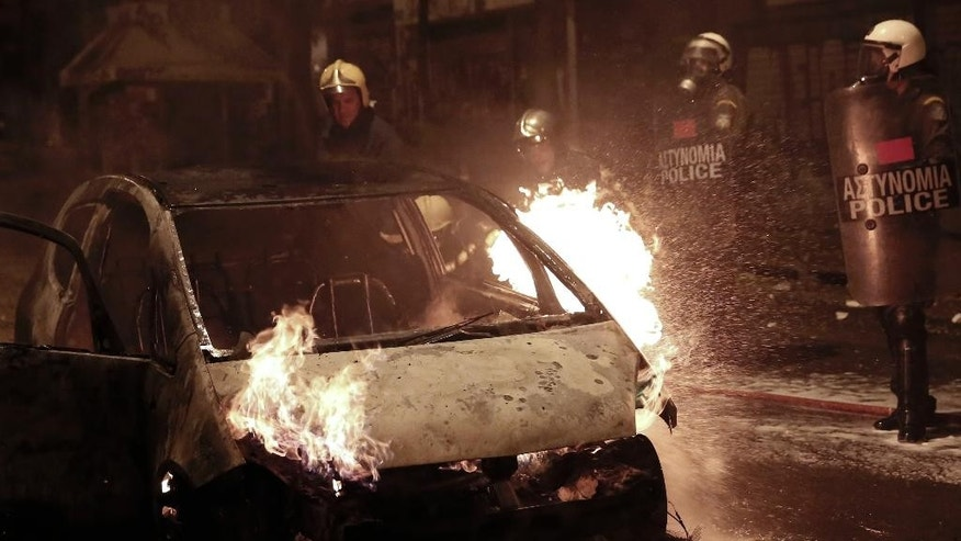 Firemen try to extinguish a car during clashes between anarchists and police in central Athens, on Tuesday, Dec 2, 2014. The violence followed a large demonstration Tuesday in support of a jailed anarchist Nikos Romanos who is on hunger strike seeking prison leave to attend university. (AP Photo/Petros Giannakouris)