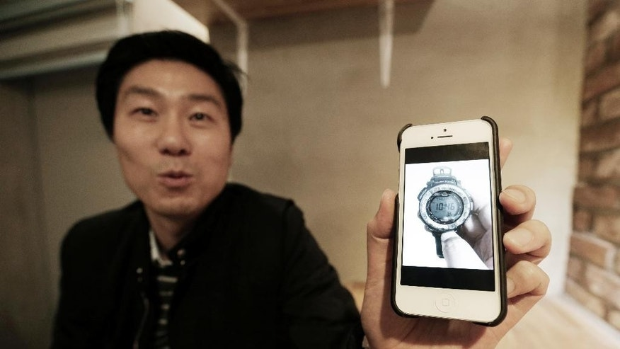 In this Nov.  28, 2014 photo,  Yoo Jung-kun, an auto industry worker, shows a picture of a wristwatch that he recently purchased on an online retailer overseas during an interview in Seoul, South Korea. South Korea does not celebrate Thanksgiving, but the hot deals at the U.S. retailers during the shopping season are changing habits of South Koreans who are fed up with marked-up prices of locally made and imported good at hometown retailers. Yoo saved more than $1,000 when he bought a LG Electronics television from Amazon this summer, even after paying $190 for shipping and $30 insurance for the $999 model (AP Photo/Ahn Young-joon)