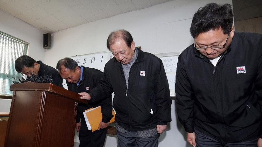 Executives of Sajo Industries bow to families of the missing fishermen of the South Korean fishing boat Oryong 501, which sank in the western Bering Sea on Dec. 1, during a briefing session at the company's branch office in Busan, South Korea, Wednesday, Dec. 3, 2014. Two more bodies have been recovered from the western Bering Sea near where the South Korean fishing ship sank earlier this week. An official from the company that owns the ship said Wednesday that the bodies appear to be from the ship. One fisherman's body was recovered Monday and seven fishermen were rescued. More than 50 are missing. (AP Photo/Yonhap, Kim Sun-ho)  KOREA OUT