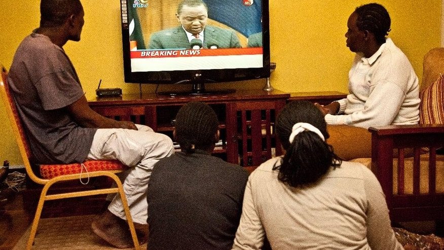 Kenyans watch national television in Nairobi, as Kenyan President Uhuru Kenyatta, addresses the nation, Tuesday, Dec. 2, 2014 on the death of Kenyan quarry workers who were killed in an attack in northern Kenya  by suspected Islamic extremists from Somalia. (AP Photo)
