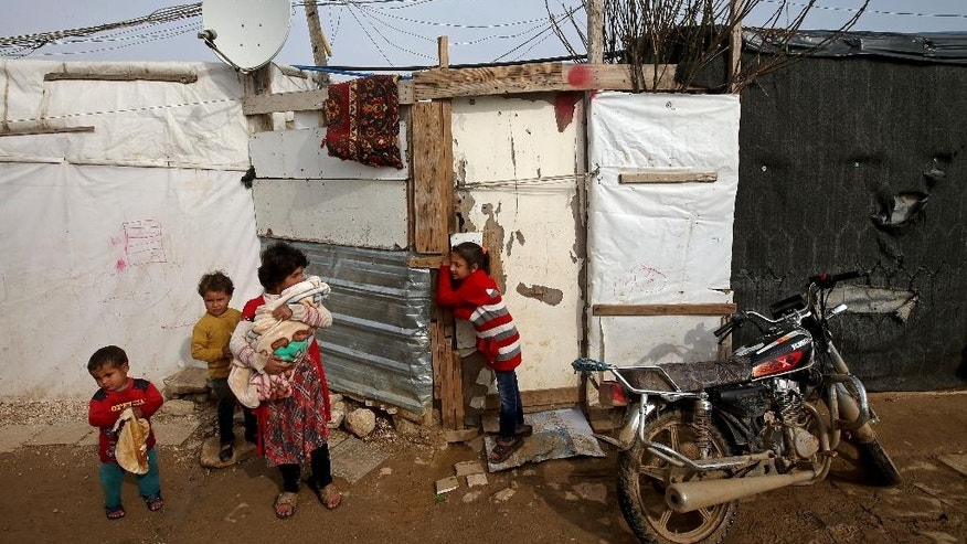 Syrian children stand outside their tent, at a refugee camp in the eastern Lebanese Town of Zahleh, Lebanon, Tuesday, Dec. 2, 2014. Syrian refugees in Lebanon reacted with panic Tuesday to news that the U.N. was suspending aid to 1.7 million refugees due to lack of funds a decision officials said threatens to starve thousands of families and add pressure on already strained hosting countries. (AP Photo/Hussein Malla)