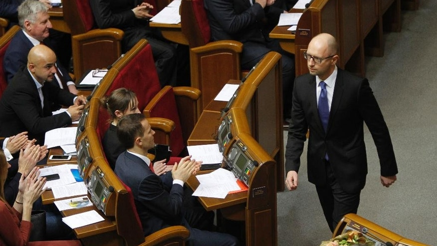 Arseniy Yatsenyuk walks in parliament shortly after giving up his position as prime minister during the inaugural sitting of the legislature in Kiev, Ukraine, on Thursday, Nov. 27, 2014. Parliament reconfirmed him as prime minister shortly afterwards. The legislature has convened for its first session since October elections that ushered in a spate of pro-Western political parties. (AP Photo/Sergei Chuzavkov)