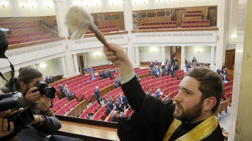 An orthodox  priest blesses the Ukrainian parliament prior a session in Kiev, Ukraine, Tuesday, Dec. 2, 2014. (AP Photo/Efrem Lukatsky)