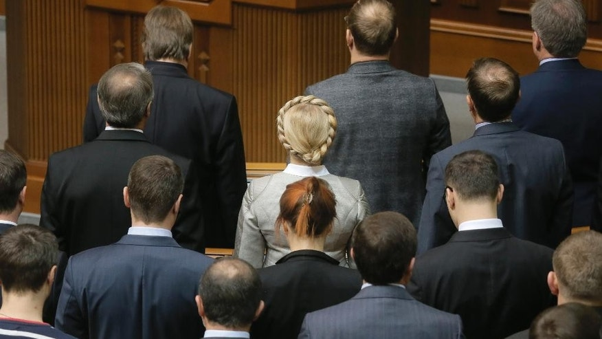 Former Prime Minister and leader of the Fatherland party Yulia Tymoshenko, center, stands with lawmakers from her party during a parliament session in Kiev, Ukraine, Tuesday, Dec. 2, 2014. The Organization for Security and Cooperation in Europe said Tuesday that under the agreement for a new cease-fire, hostilities are to cease Friday along the line of contact between the warring sides. (AP Photo/Efrem Lukatsky)