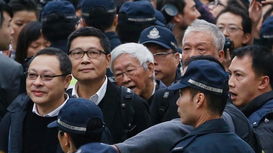 Four protest leaders, from left, Benny Tai Yiu-ting, Chan Kin-man, Joseph Zen and Chu Yiu-ming, surrounded by police officers, walk to the police station in Hong Kong as they surrender to police Wednesday, Dec. 3, 2014 to take responsibility for protests that have shut down parts of the Asian financial center for more than two months. Three founders of Hong Kong's pro-democracy protest movement called for an end to street demonstrations to prevent more violence and take the campaign to a new stage, but it wasn't clear whether student protesters, who make up the bulk of the activists, would heed the call. (AP Photo/Kin Cheung)