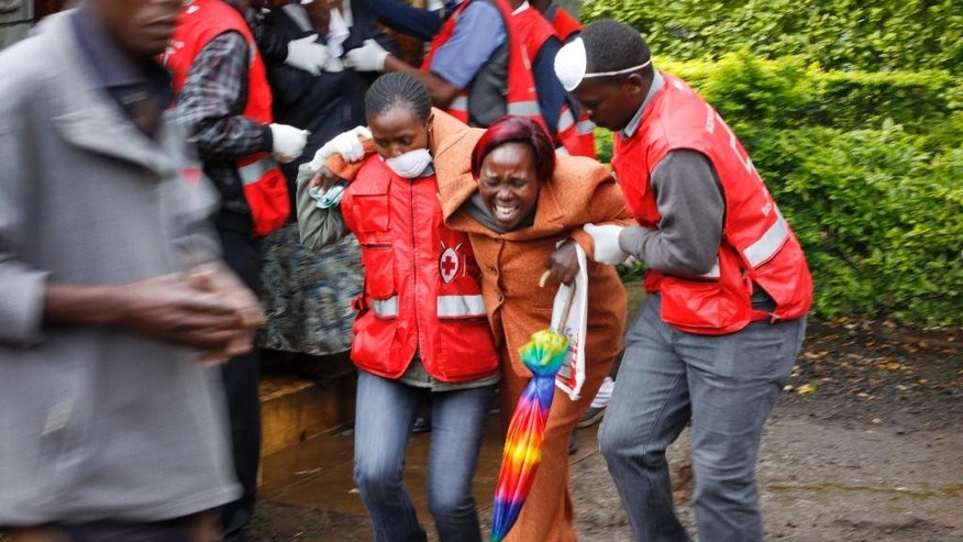 A woman is assisted by Red Cross workers as she is overcome by emotion after seeing the body of a relative who was killed in Tuesday's attack, at the mortuary in Nairobi, Kenya Wednesday, Dec. 3, 2014. The Islamic militant group al-Shabab claimed responsibility for a methodical massacre in northern Kenya early Tuesday that killed 36 non-Muslims - 10 days after a similar attack on a bus that killed 28 - and it prompted President Uhuru Kenyatta to shake up his national security team amid public outrage over the continuing violence. (AP Photo/Khalil Senosi)