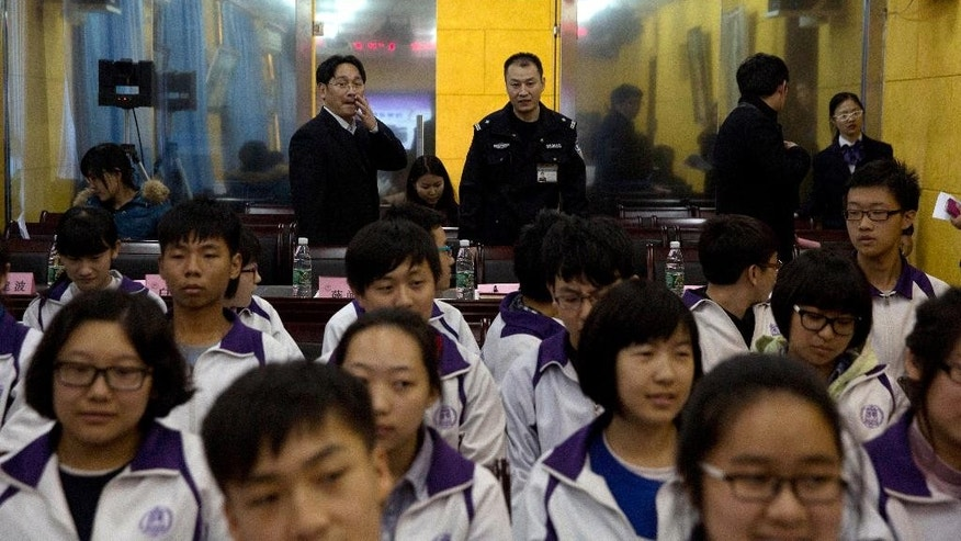 "Government workers stand under a banner which reads ""Tsinghua affiliated Chaoyang School, The Law and me together, legal series of talks"" as they observe a student meeting on legal matters coinciding with China's first Constitution Day at their school in Beijing, China, Thursday, Dec. 4, 2014. China on Thursday marked its first Constitution Day as part of President Xi Jinping's drive to show that the country embraces rule of law while ensuring that ruling Communist Party holds on to its unrivaled authority. (AP Photo/Ng Han Guan)"