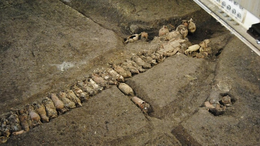 In this undated photo provided by the Cooperativa Archeologia, lined up amphoras that were discovered during a subway construction in Rome. Archaeologists have unearthed an ancient commercial farm in the heart of modern Rome, taking advantage of subway construction to explore unusually deep for urban settings. They explored some 20 meters down (around six stories deep) near St. John in Lateran Basilica. Rossella Rea, the dig's leader and a culture ministry official, said Wednesday, Dec. 3, 2014 a farm business from Imperial era Rome was discovered, along with an irrigation basin measuring 35 by 70 meters (115 feet by 230 feet) near an ancient water source known as Aqua Crabra.(AP Photo/Cooperativa Archeologia, ho)
