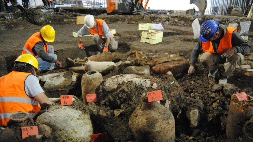 In this undated photo provided by the Cooperativa Archeologia, archeologists work next to unearthed amphoras in Rome. Archaeologists have unearthed an ancient commercial farm in the heart of modern Rome, taking advantage of subway construction to explore unusually deep for urban settings. They explored some 20 meters down (around six stories deep) near St. John in Lateran Basilica. Rossella Rea, the dig's leader and a culture ministry official, said Wednesday, Dec. 3, 2014 a farm business from Imperial era Rome was discovered, along with an irrigation basin measuring 35 by 70 meters (115 feet by 230 feet) near an ancient water source known as Aqua Crabra.(AP Photo/Cooperativa Archeologia, ho)