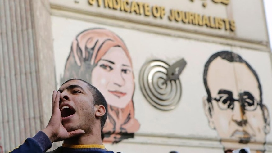 An Egyptian chants slogans denouncing toppled President Hosni Mubarak during a protest in front of the press syndicate in Cairo, Egypt, Tuesday, Dec. 2, 2014. A judge on Saturday dismissed the case against Mubarak and acquitted his security chief over the killing of hundreds of protesters during Egypt's 2011 uprising. Graffiti on the wall shows Al-Housseiny Abu Daif, right, and Mayada Ashraf, left, two journalists who were shot to death during separate clashes following the 2011 popular uprising. (AP Photo/Amr Nabil)