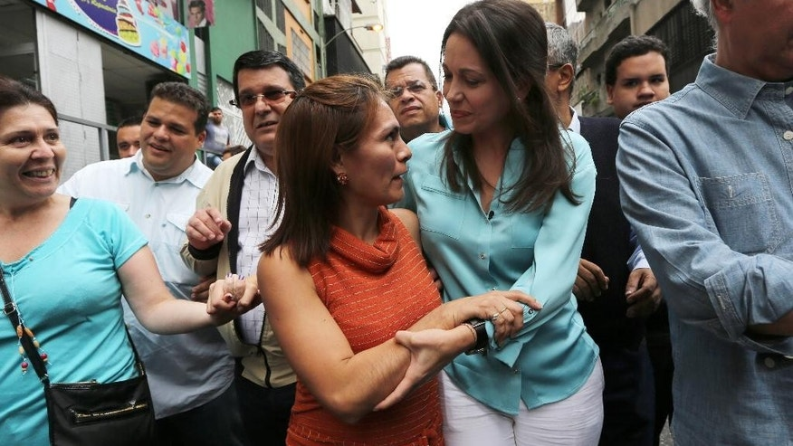 Former Congresswoman and opposition leader Maria Corina Machado, right, listens to a supporter as she arrives to the Attorney General Office to testify in Caracas, Venezuela, Wednesday, Dec. 3, 2014. Machado, 47, appeared in court to testify after being charged with conspiring to assassinate Venezuela's President Nicolas Maduro. She was prohibited from leaving the country in June after being removed from the National Assembly by the ruling party. (AP Photo/Ariana Cubillos)