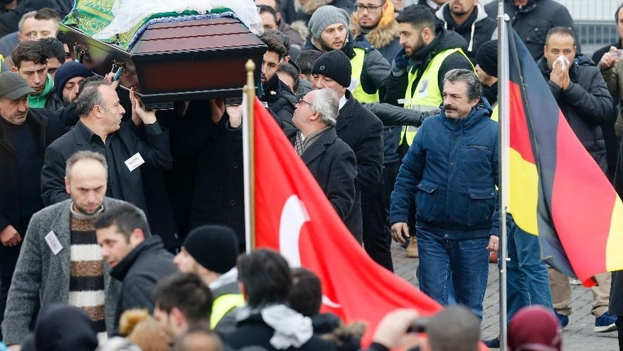 The coffin withTugce Albayrak is carried to a funeral ceremony outside a mosque in Waechtersbach, Germany, Wednesday, Dec. 3, 2014. Tugce had been in a coma since mid-November following an altercation at a restaurant in Offenbach near Frankfurt. She died Friday, her 23rd birthday, after her family gave doctors permission to switch off her life support. (AP Photo/Michael Probst)
