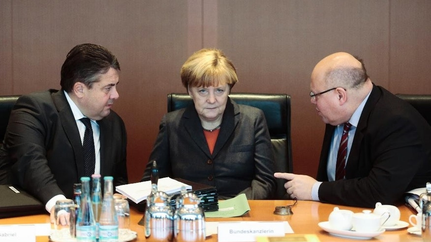 German Chancellor Angela Merkel, center, talks with Vice Chancellor and Economic and Energy Minister Sigmar Gabriel, left, and Head of the Chancellery Minister Peter Altmaier, right, during the cabinet meeting in Berlin, Germany, Wednesday, Dec. 3, 2014. The cabinet will present in the meeting laws about Germany's future energy policy and about the right of residence for immigrants. (AP Photo/Markus Schreiber)