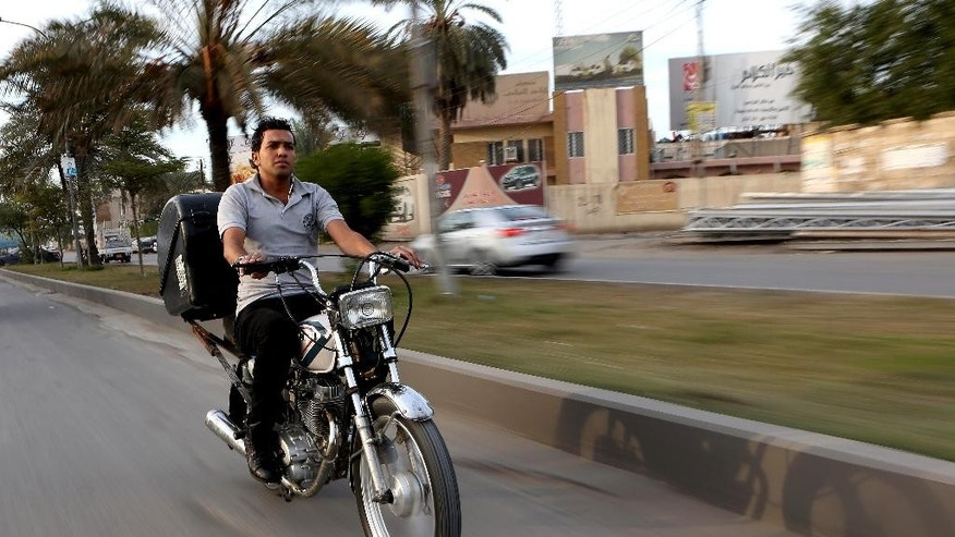 In this Sunday, Nov. 30, 2014 photo,  22-year-old Hassan Khudair, makes his way on a motorbike to deliver food, in Baghdad, Iraq. As he rushes pizza and shwarma sandwiches to waiting customers, Khudier has to deal with the countless security checkpoints in the Iraqi capital and the risk of being in the wrong place at the wrong time in a city where car bombings and suicide blasts take place nearly daily. (AP Photo/Hadi Mizban)