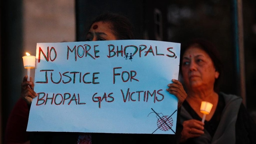 Members of a social organization participate in a candle light vigil to express solidarity with the Bhopal gas tragedy survivors on the eve of its 30th anniversary in Bangalore, India, Tuesday, Dec. 2, 2014. Thousands of people died after a cloud of methyl isocyanate gas on on Dec. 3, 1984, escaped from a pesticide plant operated by a Union Carbide subsidiary in Bhopal, central India, affecting the lives of many. (AP Photo/Aijaz Rahi)