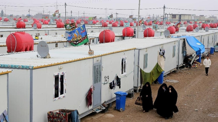 In this Thursday, Nov. 27, 2014 photo, displaced Iraqi Shiite families take shelter at the Nabi Younis refugee camp in Baghdad's southeast suburb of Nahrawan, Iraq. With a U.N.-estimated 1.8 million Iraqis displaced this year amid the war with the Islamic State group, this country upended by the 2003 U.S.-led invasion finds itself even further splintering along ethnic and religious lines. Those divisions come into focus in the experiences of its displaced. (AP Photo/Karim Kadim)