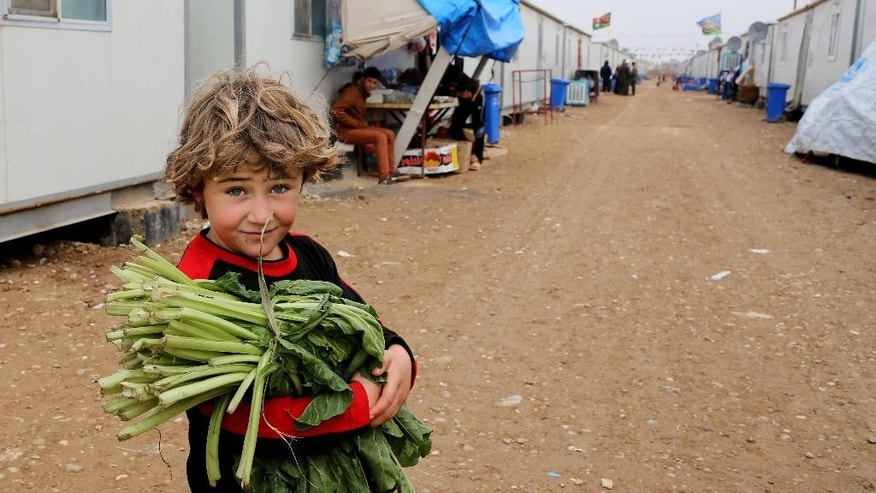 In this Thursday, Nov. 27, 2014 photo, 5-year-old Yusuf Abdul Karim brings vegetables to his family at the Nabi Younis refugee camp in Baghdad's southeast suburb of Nahrawan, Iraq. The camp has its own medical clinic and children play soccer on a nearby pitch as women sit in computer and hairdressing classes. (AP Photo/Karim Kadim)