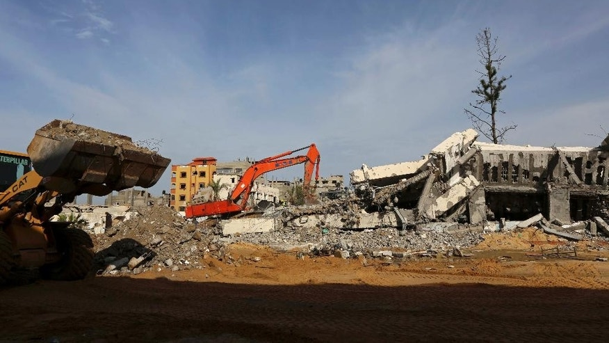 A Palestinian bulldozer and crane remove the rubble of Jamal Abdelnaser UNRWA School which was destroyed during the recent conflict between Israel and Hamas in Shijaiyah neighborhood in Gaza City, in the northern Gaza Strip, Wednesday, Dec. 3, 2014. The first large-scale project to remove rubble from the most recent war in the Gaza Strip started Wednesday, a step perceived as notable on the long path of rebuilding. Sweden is paying $3.2 million for this project through UNDP's Programme of Assistance to the Palestinian People, where officials hope to crush and clear 140,000 tons of rubble in Shijaiyah in one year. (AP Photo/Adel Hana)