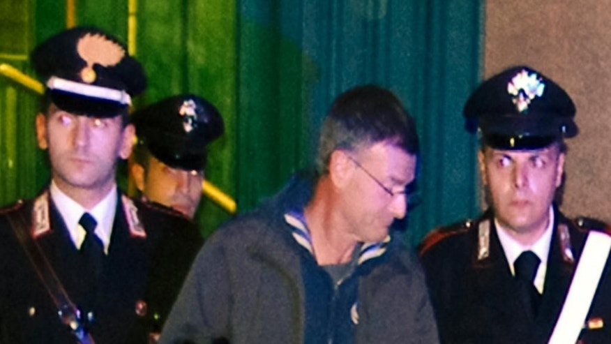 In this Dec. 2, 2014 handout photo Italian Carabinieri arrest Massimo Carminati, center, in Rome. Carminati, alleged far-right domestic terrorist in the 1970s, was arrested along with other 36 people in a sweeping probe of ties between gangsters based in the Italian capital and allegedly corrupt city politicians. Dozens of other suspects, including Gianni Alemanno, Rome's previous mayor, were formally notified they are being probed. (AP Photo/Carabinieri, ho)
