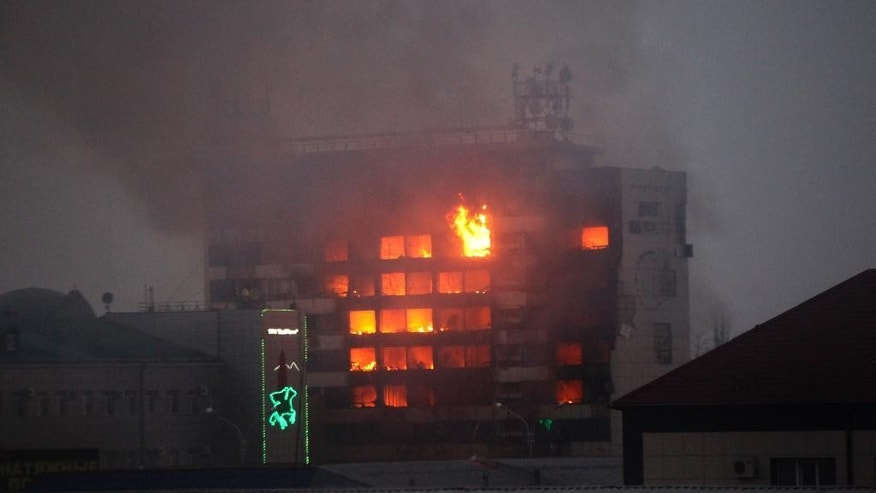 A publishing house building is seen in flames in the center of Grozny, Russia, early Thursday, Dec. 4, 2014. A gun battle broke out after midnight Thursday in the capital of Russia's North Caucasus republic of Chechnya, puncturing the patina of stability ensured by years of heavy-handed rule by a Kremlin-appointed leader. Security officials and the leader of Chechnya said gunmen traveling in several cars killed at least three traffic police officers at a checkpoint late at night in the capital of the republic, Grozny. The Moscow-based National Anti-Terrorist Committee said in a statement that after the attack on the traffic police, gunmen occupied a publishing house in the center of Grozny. It said security services, police and emergency services personnel surrounded the building. (AP Photo/Musa Sadulayev)
