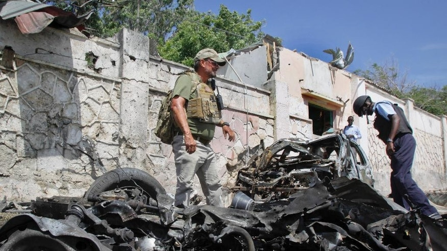 Dec. 3, 2014: A foreign security officer inspects wreckage at the scene of a suicide car bomb attack that targeted a United Nations convoy, outside the airport in Mogadishu, Somalia. (AP)