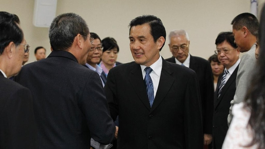 Taiwan's President Ma Ying-jeou, center, shakes hands with party members after tendering his resignation as chairman of the ruling Nationalist Party following its major defeat in island-wide local elections at the party headquarters in Taipei, Taiwan, Wednesday, Dec. 3, 2014. China called on Taiwan on Wednesday to stay the course of deepening exchanges between the sides after a stunning electoral defeat for the island's ruling pro-China Nationalist Party. (AP Photo/Wally Santana)