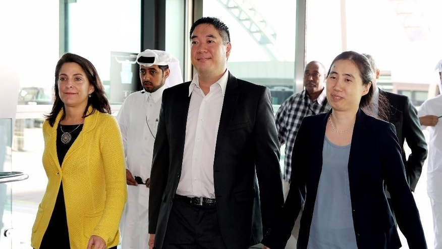 American couple Grace, center, and Matthew Huang, right, walk to their departure gate with U.S. Ambassador to Qatar, Dana Shell Smith, left, at the Hamad International Airport in Doha, Qatar, Wednesday, Dec. 3, 2014. An American couple cleared of charges in their adopted daughter's death passed through passport control Wednesday and are set to leave Qatar. (AP Photo/Osama Faisal)