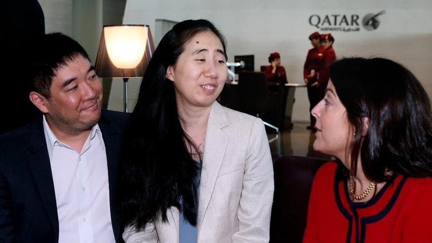 American couple Grace, center, and Matthew Huang, left, speak with U.S. Ambassador to Qatar, Dana Shell Smith, right, at the Hamad International Airport in Doha, Qatar, Wednesday, Dec. 3, 2014. An American couple cleared of charges in their adopted daughter's death passed through passport control Wednesday and are set to leave Qatar. (AP Photo/Osama Faisal)