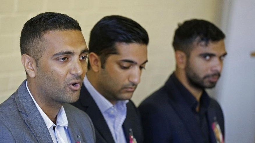 """Anish Hindocha, the brother of Anni Dewani who was murdered during her honeymoon in South Africa in 2010, arrives at a press conference with other family members in the city of  Cape Town, South Africa, Wednesday, Dec. 3, 2014. With his sister's photograph pinned to his jacket, Anish Hindocha on Wednesday asked his sister's husband to tell the """"full story"""" of how she was murdered while on honeymoon in Cape Town. (AP Photo/Schalk van Zuydam)"""