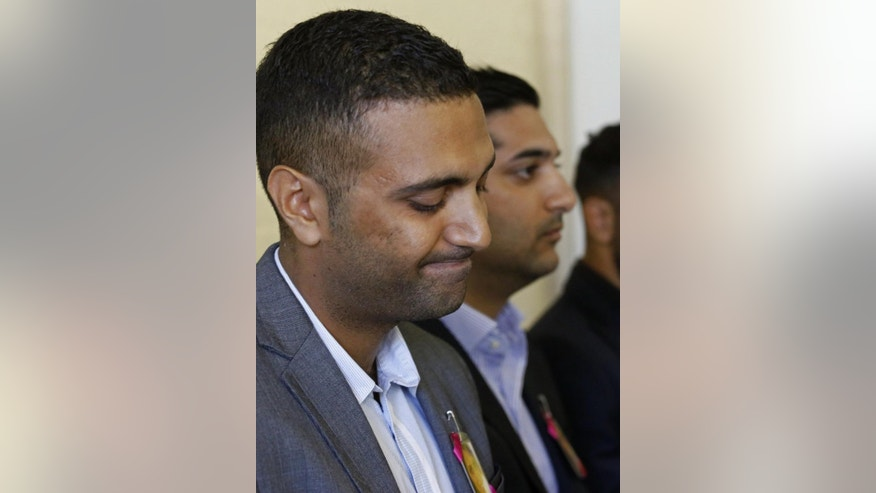 """Anish Hindocha, the brother of Anni Dewani who was murdered during her honeymoon in South Africa in 2010, looks down during a press conference with other family members in the city of Cape Town, South Africa, Wednesday, Dec. 3, 2014. With his sister's photograph pinned to his jacket, Anish Hindocha on Wednesday asked his sister's husband to tell the """"full story"""" of how she was murdered while on honeymoon in Cape Town. (AP Photo/Schalk van Zuydam)"""