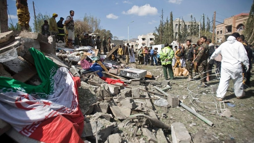 An Iranian flag, left, lies on the ground as police troopers gather at the residence of the Iranian ambassador after a car bomb attack in Sanaa, Yemen, Wednesday, Dec. 3, 2014. A massive car bomb exploded Wednesday morning in the Yemeni capital, Sanaa, apparently targeting the home of the Iranian ambassador, Yemeni security officials said. (AP Photo/Hani Mohammed)