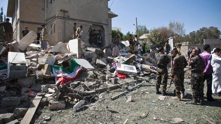An Iranian flag, left, lies on ground as police troopers gather at the residence of the Iranian ambassador after a car bomb attack in Sanaa, Yemen, Wednesday, Dec. 3, 2014. A massive car bomb exploded Wednesday morning in the Yemeni capital, Sanaa, apparently targeting the home of the Iranian ambassador, Yemeni security officials said. (AP Photo/Hani Mohammed)