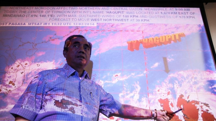 Alexander Pama, chief of the National Disaster Risk Reduction Management Council, points to the satellite image of Typhoon Hagupit which is brewing over the Pacific Ocean during a media briefing on the Government agency's readiness in dealing with a possible strong weather disturbance Wednesday, Dec. 3, 2014 at suburban Quezon city northeast of Manila, Philippines. The Philippines weather bureau is advising the public to brace for Typhoon Hagupit which continues to gead towards the central Philippines and looking at the possibility it might hit the same areas as super Typhoon Haiyan which devastated Tacloban last year. (AP Photo/Bullit Marquez)