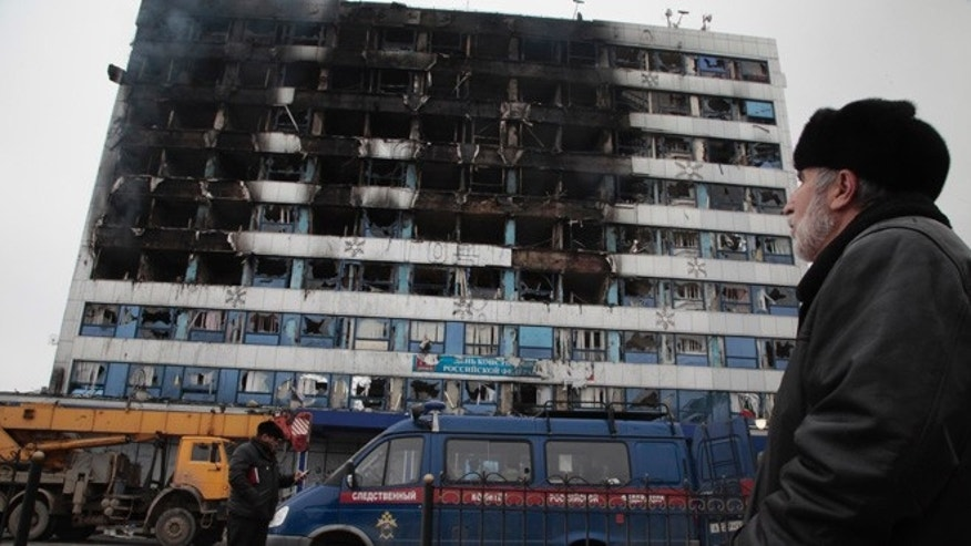 Dec. 4, 2014: An investigative committee minivan is pictured parked outside a burned publishing house in central Grozny, Russia. A gun battle broke out early Thursday in the capital of Russia's North Caucasus republic of Chechnya, puncturing the patina of stability ensured by years of heavy-handed rule by a Kremlin-appointed leader. The violence erupted hours before Russian President Vladimir Putin began his annual state of the nation address in Moscow.